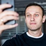 Навальный Алексей смотрит в iphone